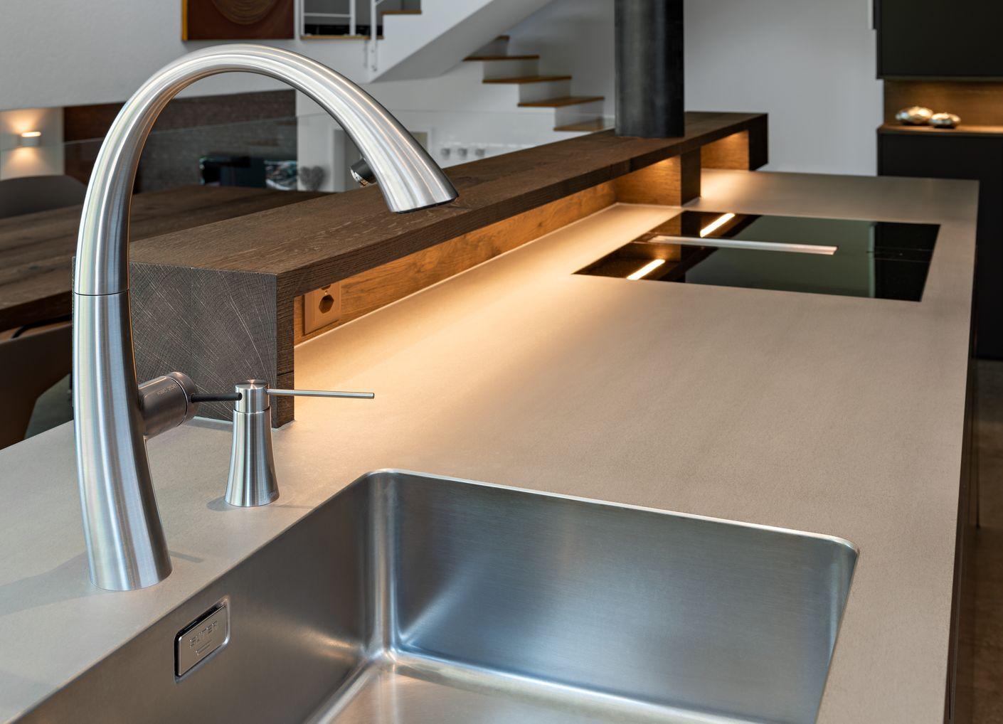 Ein Blickfang ist die anmutige Armatur ZOE mit dem Seifenspender im gleichen Design. Das dimmbare Licht an der Theke beleuchtet die Arbeitsfläche mit dem BORA Kochfeld.