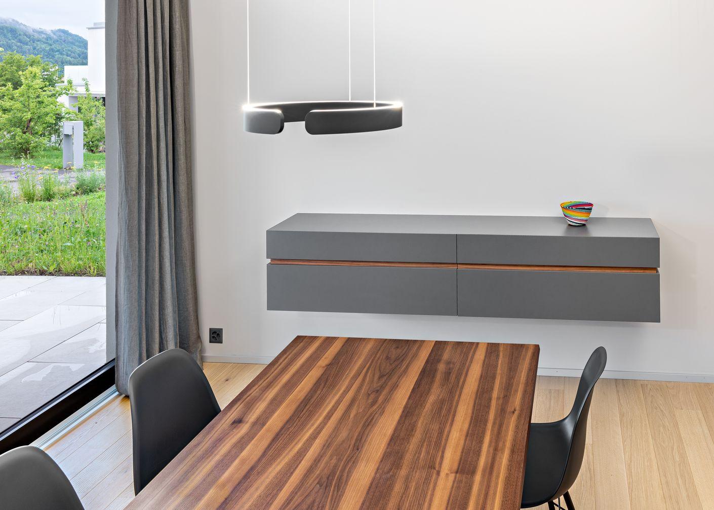 Ein Hingucker! Wandboard mit durchgehender Ziernut aus Holz, passend zum Tisch. Links befinden sich zwei leise schliessende Schubladen, rechts eine Klappe für die Hausbar. Idee und Konzept: Zahner Interiors GmbH Zürich, Matthias Zahner