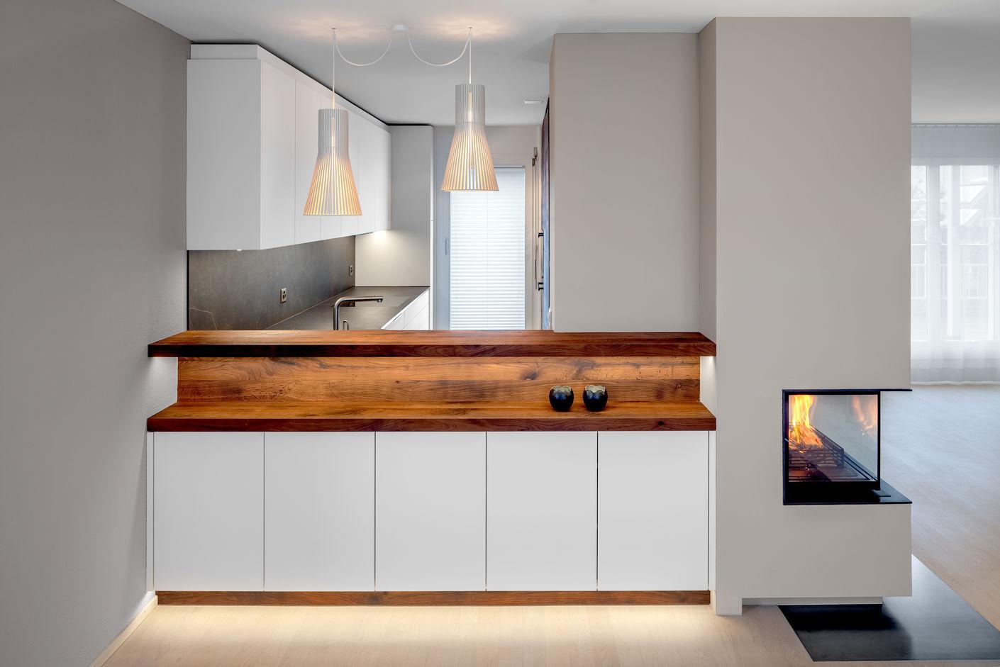 Neben der beleuchteten Theke ist das integrierte Cheminée ein Hingucker. Es verleiht der Küche einen einzigartigen Charakter und schafft den fliessenden Übergang zum Wohnbereich.