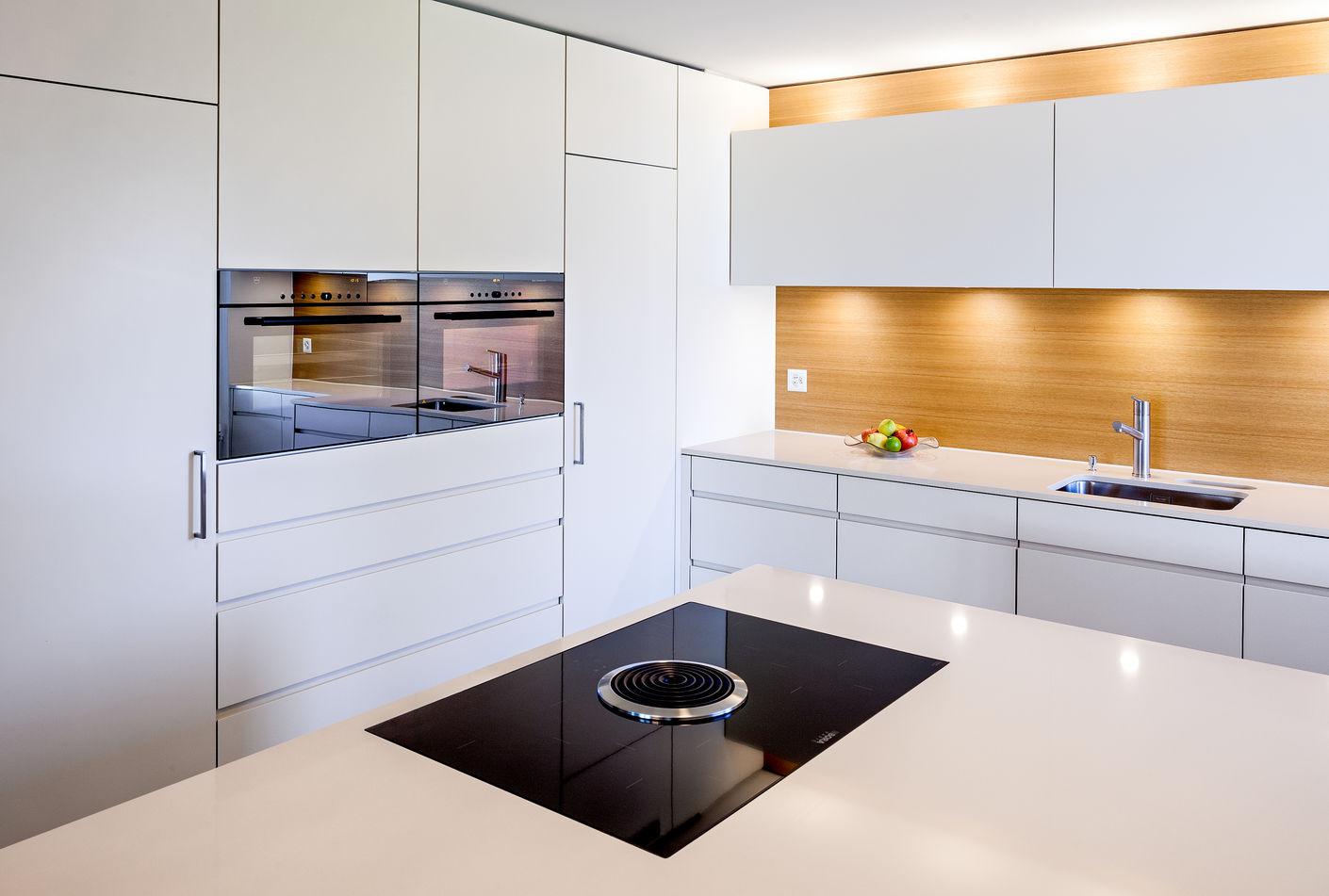 Moderne Technik und Lichteffekte: Das BORA Kochfeld mit Dampfabzug ist unscheinbar in die Kochinsel integriert. Harmonisch fügen sich die Arbeitsflächen aus poliertem Silestone ein und erzeugen Lichtspiele auf ihrer Oberfläche.