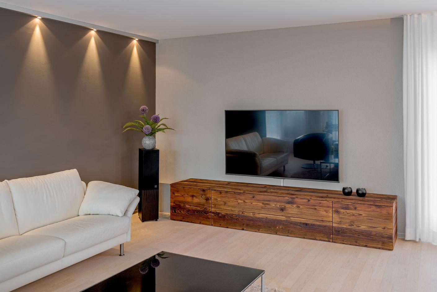 Der Blickfänger im Wohnraum: Sideboard aus trendigem Altholz. Hinter der farbigen Wand mit dem stimmungsvollen Licht verbirgt sich eine Liftschachtverkleidung aus Holz, um die Geräusche des Liftes zu dämmen.