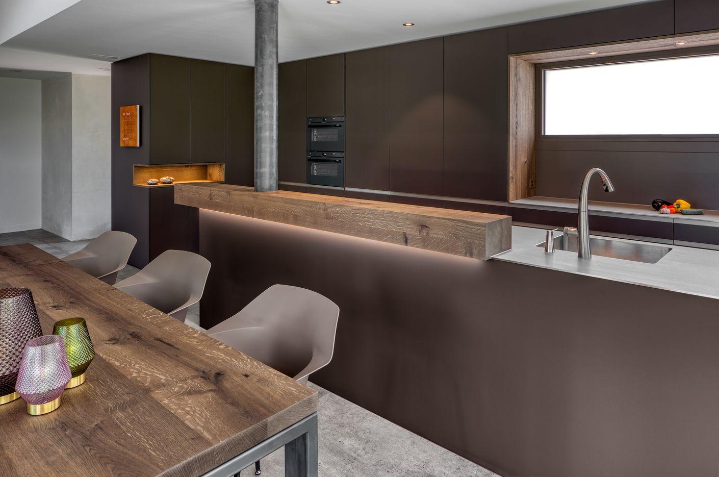 Als Kontrast zum Schokobraun der Fronten ist die Arbeitsfläche der Kücheninsel aus einer Edelstahlplatte mit eingeschweisstem Spülbecken. Die Theke und der Esstisch sind aus Altholz.