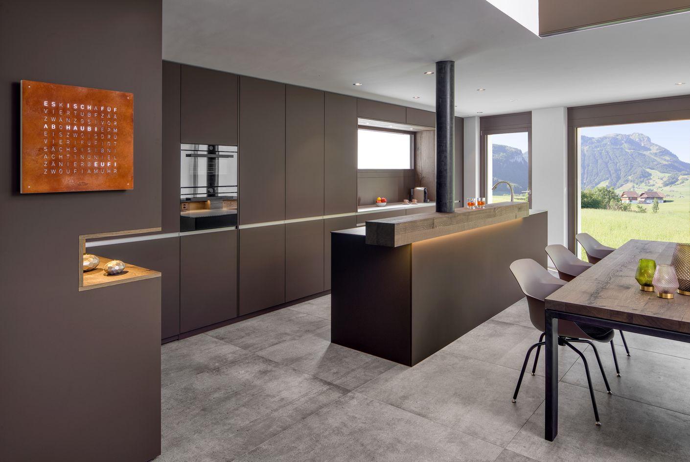 Der Zugang in den angrenzenden Vorratsraum ist raffiniert in die Küchenfront integriert und somit versteckt! Keine Türe stört die Optik, die Küchenfront erscheint wie aus einem Guss.