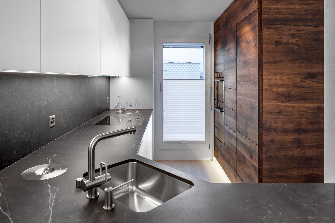 Die grifflosen Küchenfronten sind in einem zeitlosen Mattweiss gehalten. Sie vergrössern den schmalen Raum optisch. LED-Lichtbänder setzen gekonnt Akzente und lassen die grifflosen Schrankelemente aus Altholz schweben.